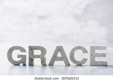 Word GRACE made with cement letters on grey marble background. Copy space. Biblical, spiritual or christian reminder.