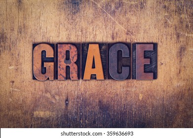 "The word ""Grace"" written in dirty vintage letterpress type on a aged wooden background."