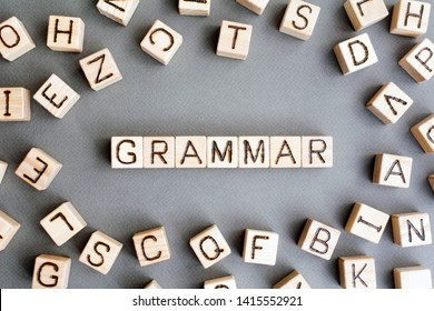 the word grammar wooden cubes with burnt letters, study of grammar of different languages,  gray background top view, scattered cubes around random letters