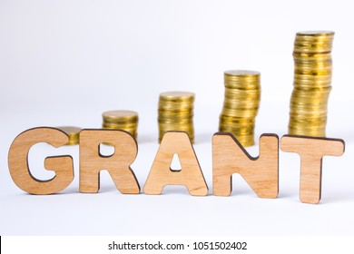Word grant of three-dimensional letters is in foreground with growth columns of coins on blurred background. Monetary grant concept for starting or development of business, startup, science, trials