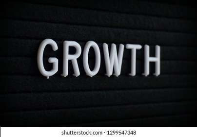 The word Growth in white plastic letters on a felt notice board