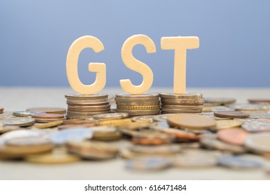 The word GST (Goods and services tax) on stack of coins over blue background