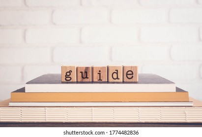 The word GUIDE, alphabets on wooden rubber stamps on top of books with bricks background, blank copy space, vintage minimal style. Concepts of instruction, learning, manual, policy, and education.