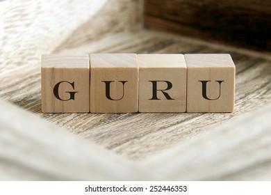 the word of GURU on wooden cubes