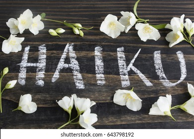 Word Haiku, Japanese Poetry, with Jasmine Flowers on a Rustic Wooden Background.