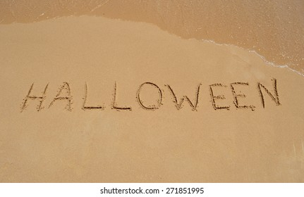 The word 'Halloween' written in the sand at the beach