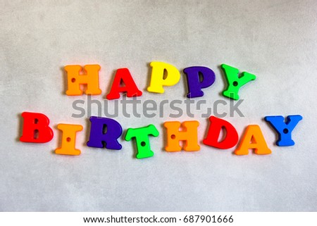 word happy birthday written with colorful plastic letters with grey background
