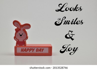 The word Happy Day is written on a wooden block and a wooden block of a rabbit cartoon. There is the text Looks Smiles and Joy.