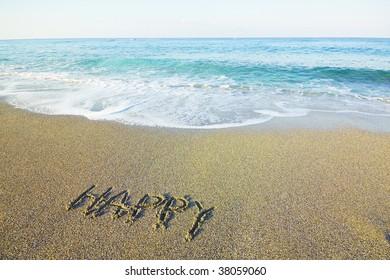 "word ""happy"" written on beach sand and sea"