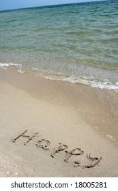 Word happy written on sand on seacoast
