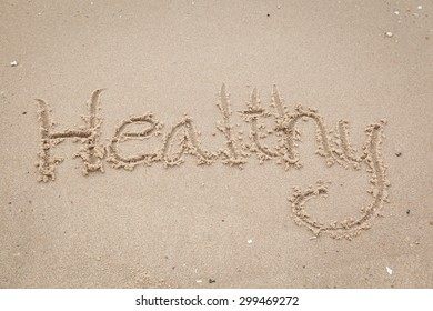 """The word with hashtag """"Healthy"""" in the sand against the sea"""