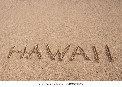 The word HAWAII is written on the beach with room for text or copy space.