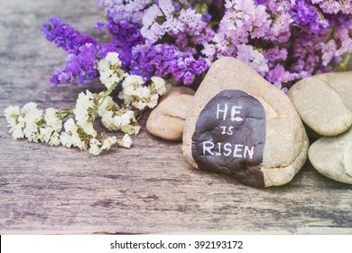 """Word  """"He is risen"""" by hand painted on the river stone with colorful flowers on wooden background, Christian concept, Easter background"""