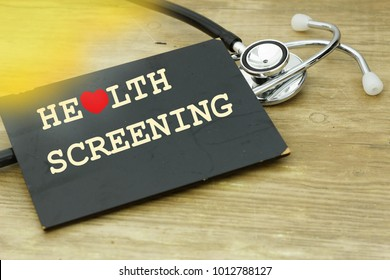 Word HEALTH SCREENING written on a small board with stethoscope and light leak