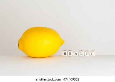 """Word """"health """" spelled by dice near yellow lemon as meaning of healthy food"""
