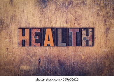 "The word ""Health"" written in dirty vintage letterpress type on a aged wooden background."