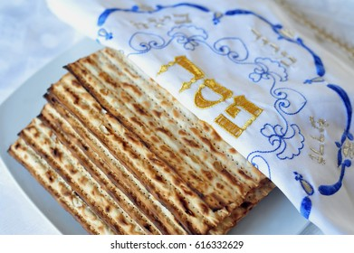 The word in Hebrew Pesach (Passover) with Matzos for Jewish Holiday Passover. Matzo is an unleavened flatbread part of Jewish cuisine of Passover festival. Food background and texture