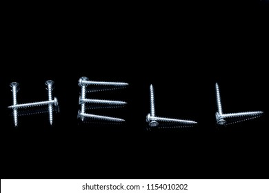 The word hell written with screws on a black background with reflections