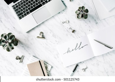 Word hello. Flat lay, top view office table desk. Workspace with laptop, diary, succulent and clips on marble background.