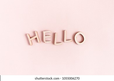 Word Hello made of wooden letters on a pale pink pastel background
