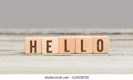 Word Hello on wood cube dices on aged table.