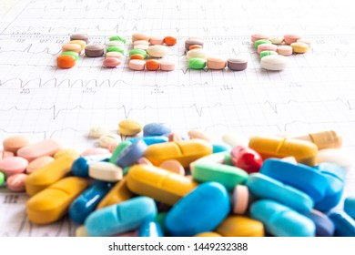 "The word ""help"" written with colored pills on electrocardiogram strips. Concept of uncertainty and drug addiction. Medical office. Doctor bewildered."