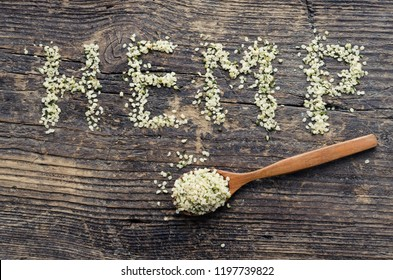 Word HEMP made of hemp seeds on old wooden background. Organic blanched hemp seeds in a spoon on rustic wooden table. Healthy eating supplement. Superfood concept. Top view.