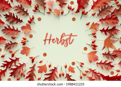 Word Herbst surrounded by assorted, various red Autumn leaves. Paper text Herbst means Autumn in German language. Simple seasonal design from natural materials.Top view, flat lay, toned image. - Shutterstock ID 1988411225