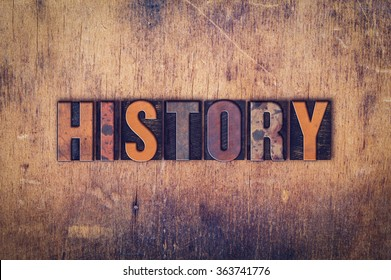 "The word ""History"" written in dirty vintage letterpress type on a aged wooden background."