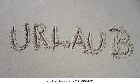 """Word Holidays german """"Urlaub"""" written in Sand - Shutterstock ID 2002906160"""