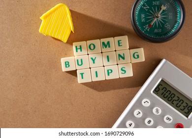 Tipps zum Kauf von Wort-Haus-Immobilien auf Quadratblöcken mit Modellhaus und Taschenrechner