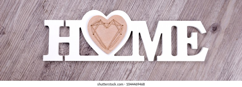 The word Home in white letters on dark wood background