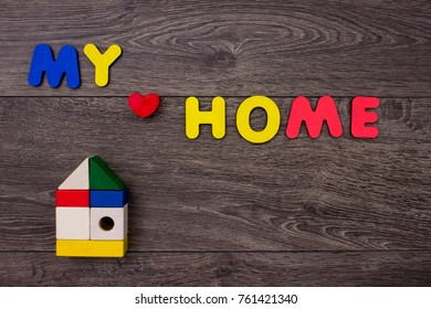 Word Home from wooden letters on wooden background