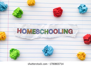 The word Homeschooling written on a lined notebook sheet with some crumpled paper balls around it. Close up.