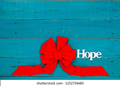 The word Hope and large red  Christmas bow hanging on rustic teal blue wood sign; religious holiday background with copy space