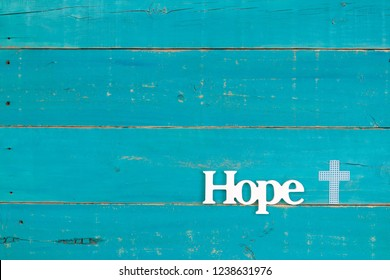 The word Hope and white cross hanging on rustic teal blue wood sign; religious holiday background with copy space