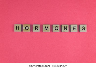 Word hormones. The phrase is laid out in wooden letters. Top view. Motivation. Women Health. Pink background. Copy space.
