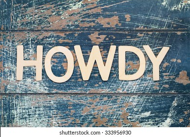 Word howdy written with wooden letters on rustic surface