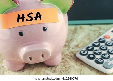 word HSA on note paper on piggy bank calculator blackboard background