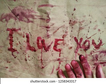 """A word """"I LOVE YOU"""" is written by a scary dead hand which colored by red color blood."""