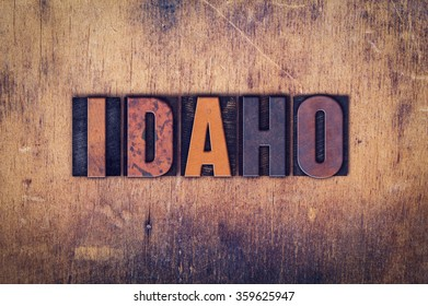 """The word """"Idaho"""" written in dirty vintage letterpress type on a aged wooden background."""