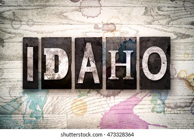 """The word """"IDAHO"""" written in vintage dirty metal letterpress type on a whitewashed wooden background with ink and paint stains."""