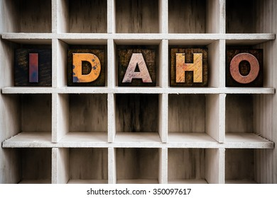 """The word """"IDAHO"""" written in vintage ink stained wooden letterpress type in a partitioned printer's drawer."""
