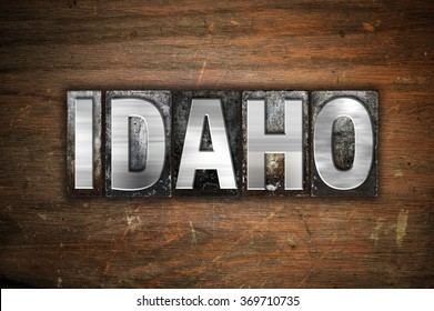 """The word """"Idaho"""" written in vintage metal letterpress type on an aged wooden background."""