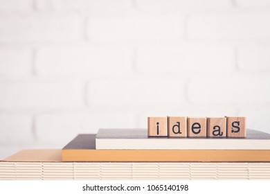 The word Ideas, alphabet on wooden rubber stamps on top of books and table. Background copy space, vintage minimal style. Creative innovation, success vision and business brainstorming concepts.