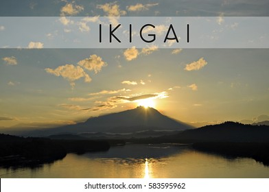 Word IKIGAI with beautiful backgound of sun coming out from behind the peak of Mount Kinabalu. Concept idea for success, business, motivation, struggle, growth and accomplishment.