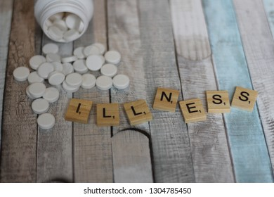 Word ILLNESS written with Scrabble letters with spilled bottle of pills/tablets on vintage wooden table. Medical disorder and health problems. Editorial image, close up photo, studio shot.