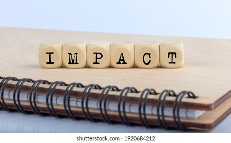 word IMPACT made with letters on wooden blocks on the wooden notepad