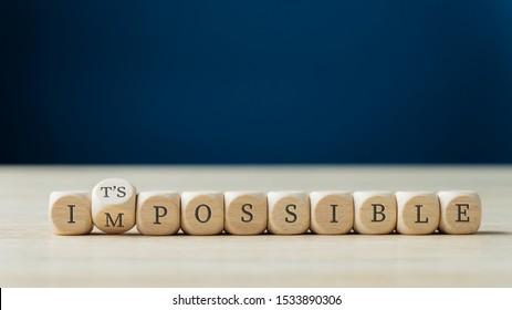 Wort unmöglich geschrieben auf hölzerne Würfel, die zweite dreht sich, um das mögliche Zeichen zu buchstabieren.