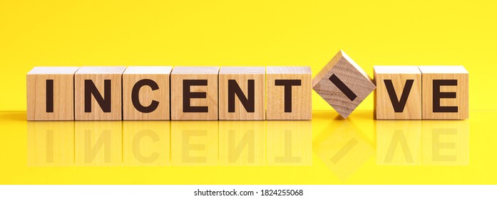 Word INCENTIVE is made of wooden building blocks lying on the table and on a light yellow background. Concept.